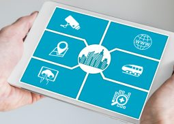 Smart city concept. Hand holding tablet or smart phone with icons of connected devices.